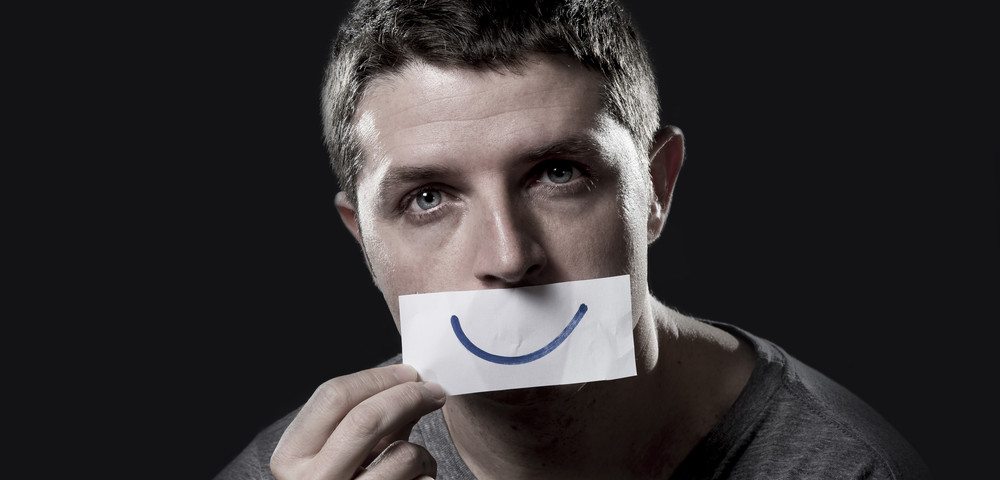 молодой парень, имитация улыбки, via shutterstock