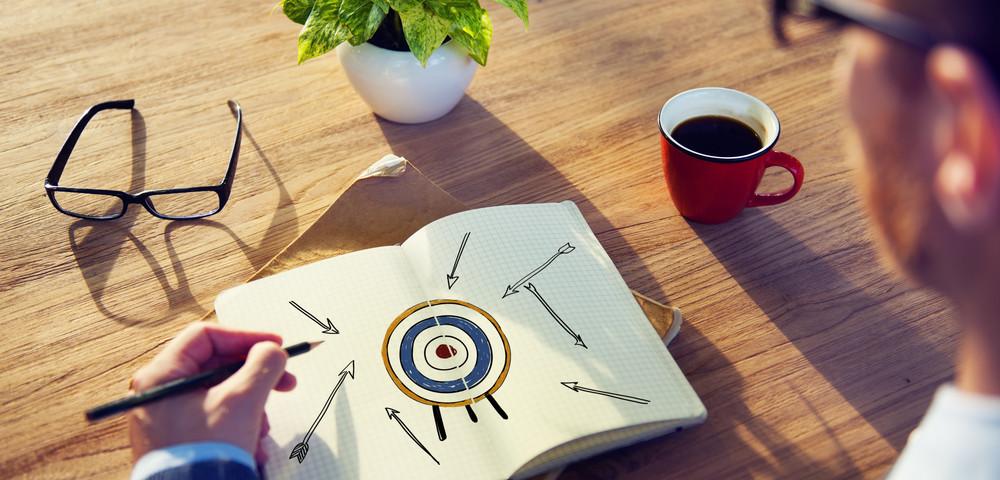 мужчна нарисовал цель и стрелы, via shutterstock