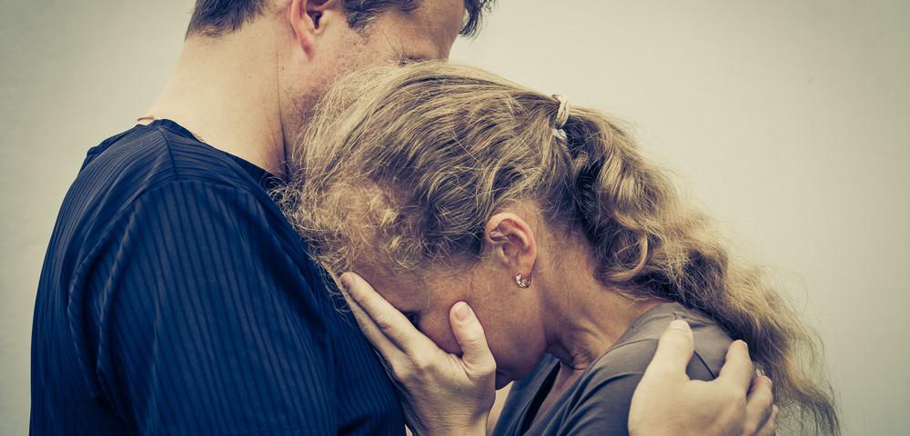 девушка плачет упершись в мужчину, via shutterstock