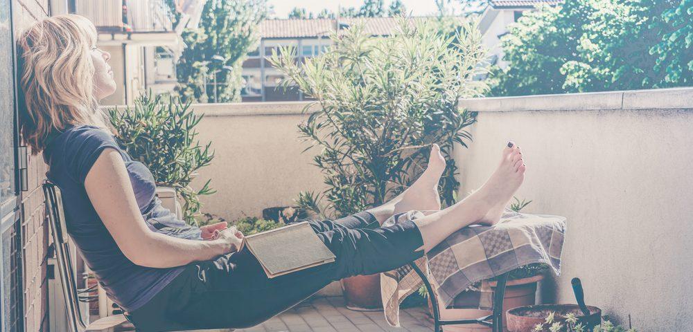 девушка с книгой на террасе, via shutterstock