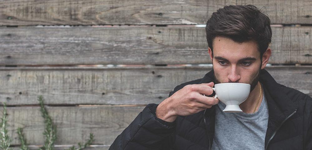 Мужчина пьет чай на улице