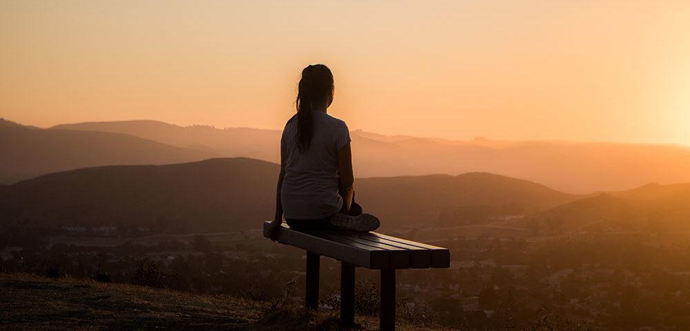 Девушка сидит и смотрит в закат